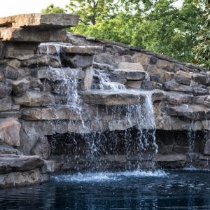 traditions pools & landscape bryan college station texas - pool project with rock & waterfall