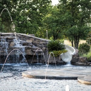 traditions pools & landscape bryan college station texas - pool project with rock, foundains, slide & waterfall