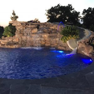 traditions pools & landscape bryan college station texas - pool construction with rock wall waterfall fountain & waterslide