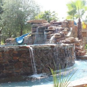 traditions pools & landscape bryan college station texas - pool project with slide, rock & landscaping 2