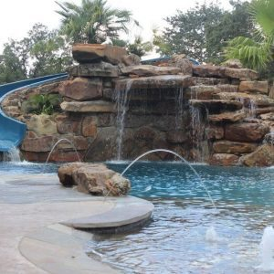 traditions pools & landscape bryan college station texas - pool project with slide, rock, waterfall & landscaping