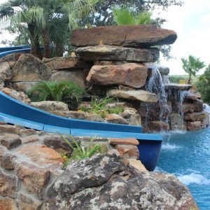traditions pools & landscape bryan college station texas - pool project with slide, rock & landscaping